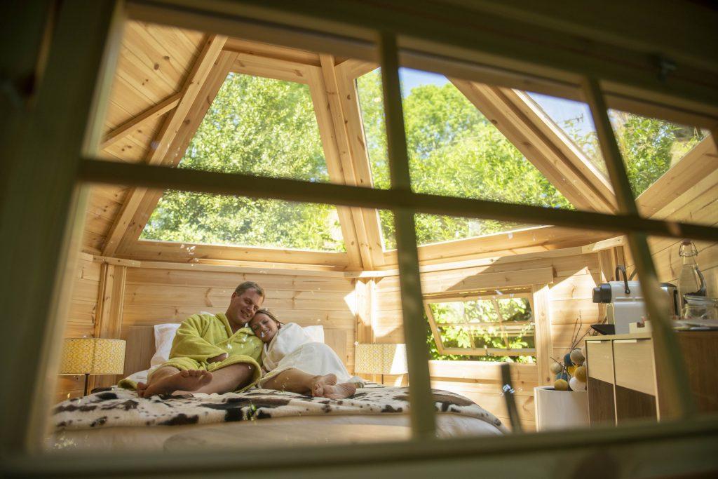 Couple dans le salon de la bulle de rêve du camping Pré des moines