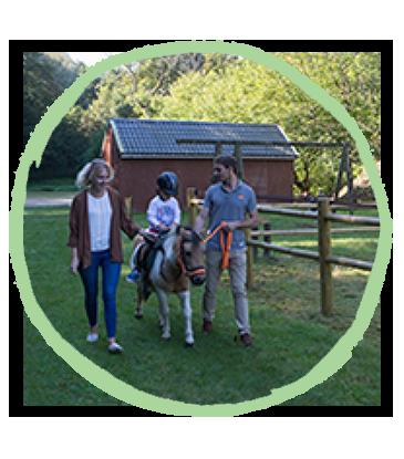Fille qui fait du poney avec sa mère au camping Pré des moines