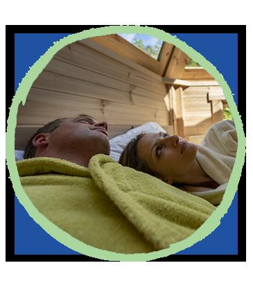 Couple qui se reposent dans la bulle de rêve du camping Pré des moines