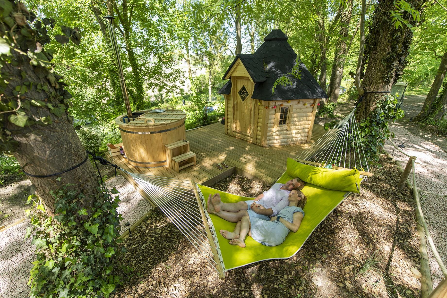 Couple dans un hamac de la bulle de rêve du camping Pré des moines