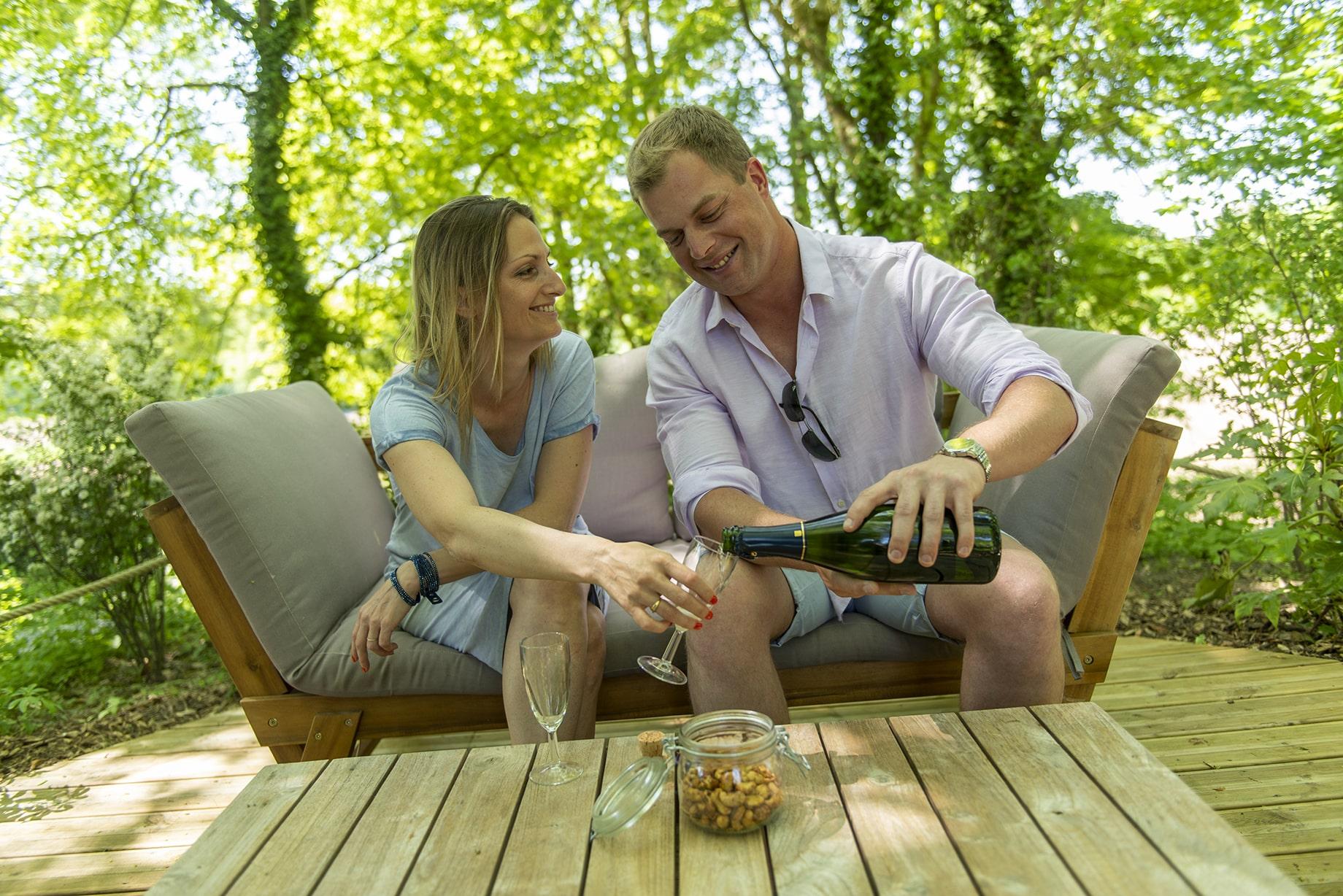 Couple qui boit du campagne dans un canapé de la bulle de rêve du camping Pré des moines