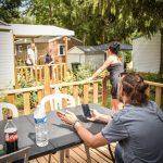 Famille sur une terrasse d'un mobil home du camping Pré des moines