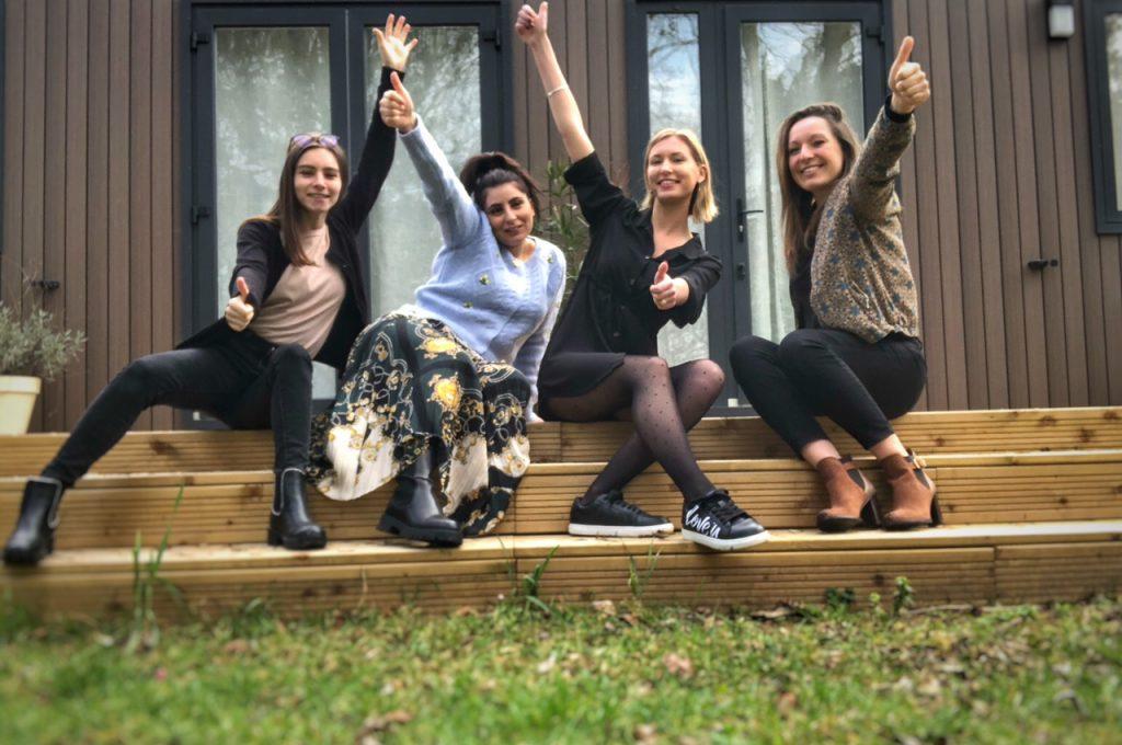 4 women sitting on stairs